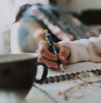 Woman writing in journal in home
